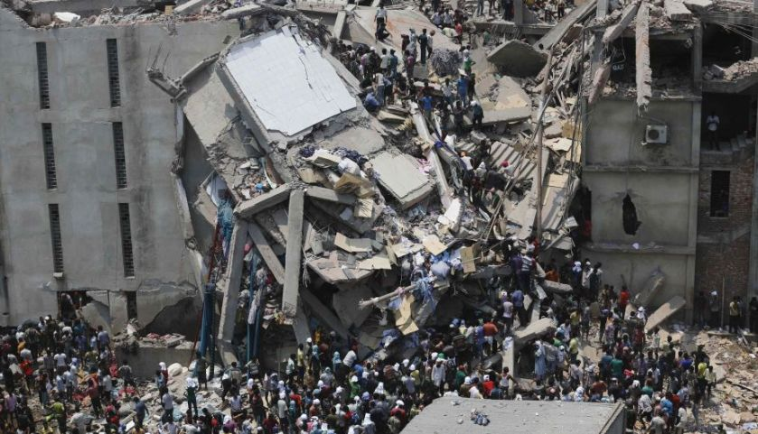 People rescue garment workers trapped under rubble at the Rana Plaza building after it collapsed, in Savar